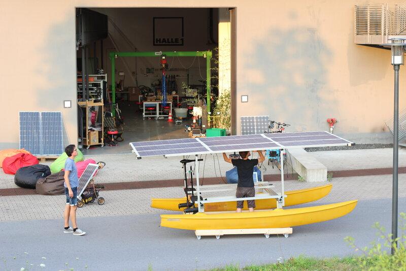 Eingang Halle 1: Menschen tüfteln an einer Solarenergie-betriebenen Erfindung
