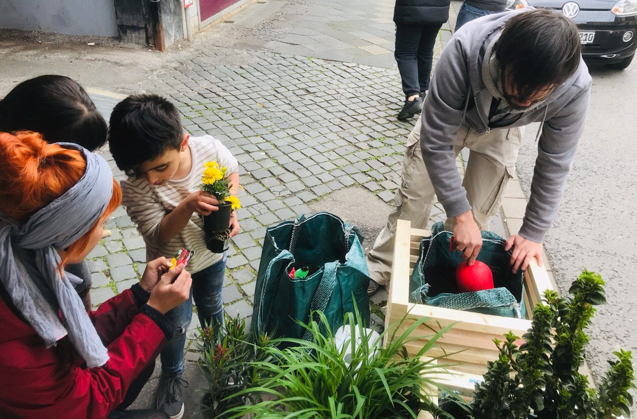 Kinder und Erwachsene pflanzen gemeinsam Pflanzen in selbstgebauten Blumenkisten ein