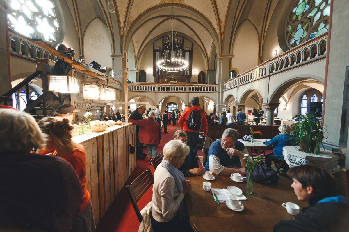 Menschen treffen sich zum Kaffee in einer umgenutzten Kirche