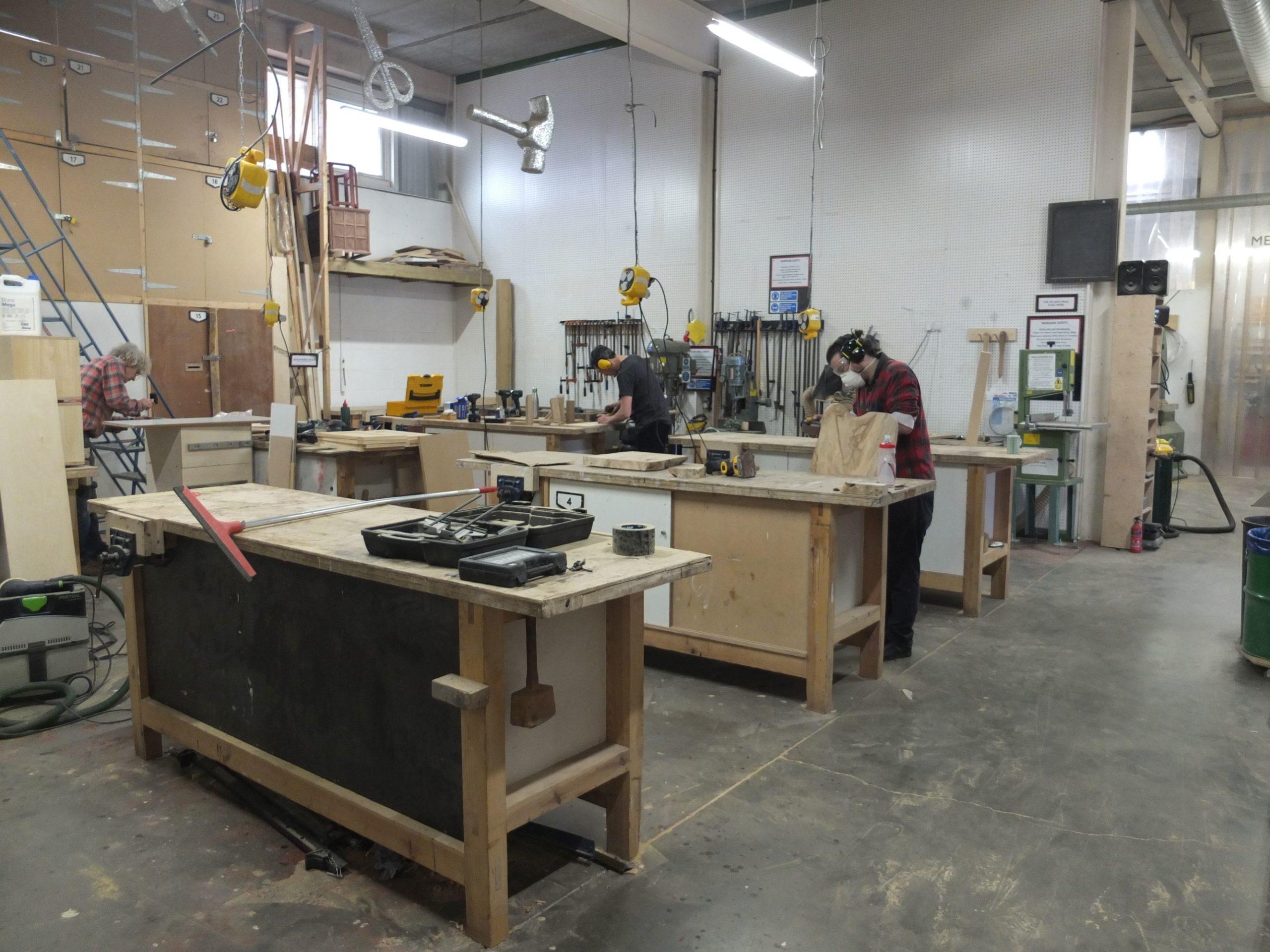 Menschen bauen mit Holz in einer Werkstatt