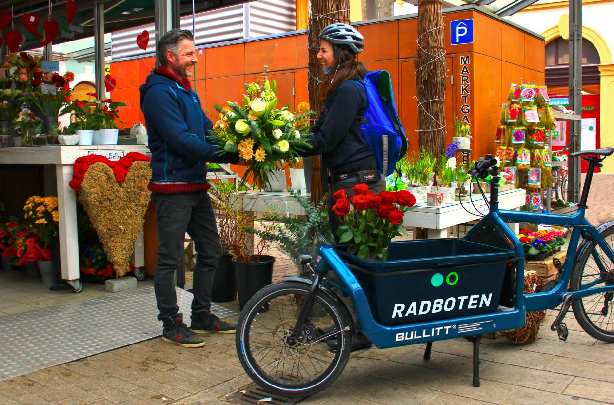 Frau holt Blumen für die Lieferung mti den Radboten ab